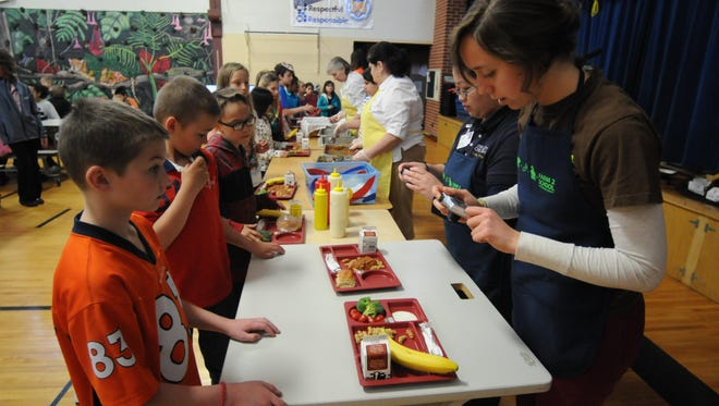Sabina Bastias takes photos of Emmeline Cook Elementary students lunches before they eat in Oshkosh. The consumption and waste is monitored and recorded by the re:TH!nk Farm To School program.