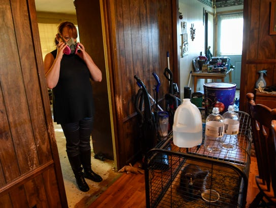 Maria McClure wears a gas mask as she cleans out her