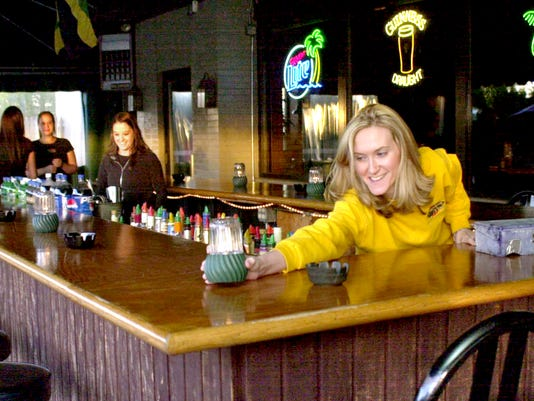 Jessica Breeden, a server for Banana Max, sets out candles around the bar before the evenings guest start to come in this file photo. The bar and grill is moving back to its original Eastern Boulevard location.