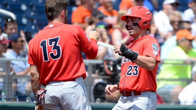 Arizona Wildcats outfielder Zach Gibbons greets infielder Cody Ramer after scoring a run in the first inning against the Oklahoma State Cowboys in the 2016 College World Series at TD Ameritrade Park.