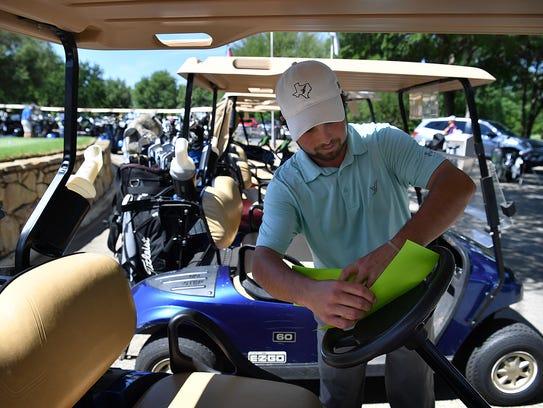 Jared Baker, golf shop assistant, places scorecards