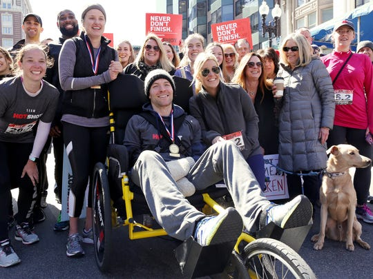 Kaitlyn Kiely and her boyfriend, Matt Wetherbee, pose for a photo with family, friends and supporters after crossing the Boston Marathon finish line, Monday, April 09, 2018.