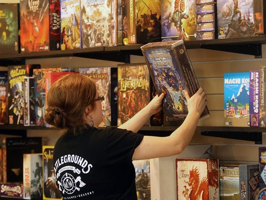 Battlegrounds Cafe's Amber Southerly removes a game from the shelves for customers to play.