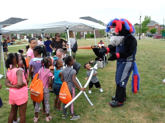 Detroit Pistons mascot Hooper greets children waiting in line for balloons at the Gleaner's kickoff event Saturday.