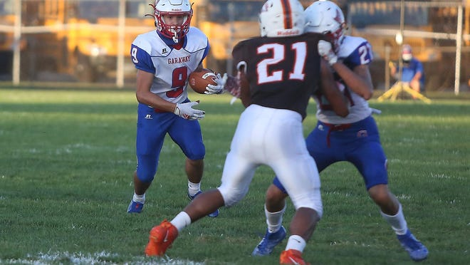 Garaway's Ethan Miller (9) follows a block from a teammate while running against Claymont Friday night.