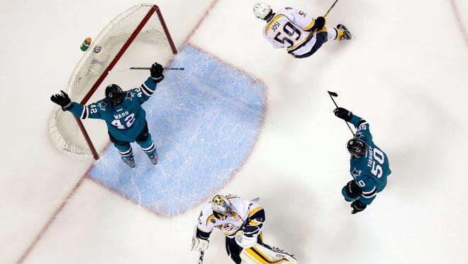 San Jose Sharks' Joel Ward, left, celebrates after scoring past Nashville Predators goalie Pekka Rinne, bottom center, and defenseman Roman Josi (59) during the first period in Game 7 of the Western Conference finals on May 12, 2016.