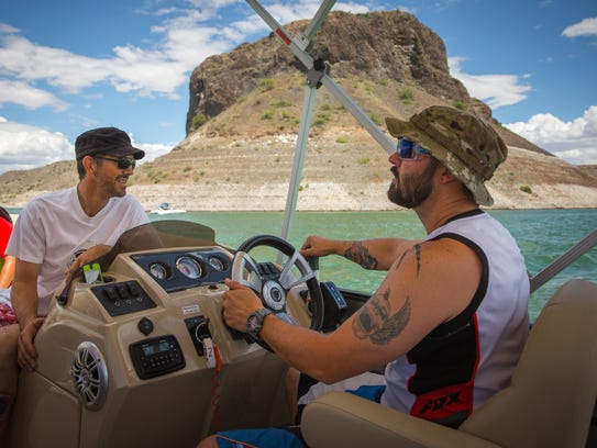 Cody Samson, right, steers a boat on Elephant Butte