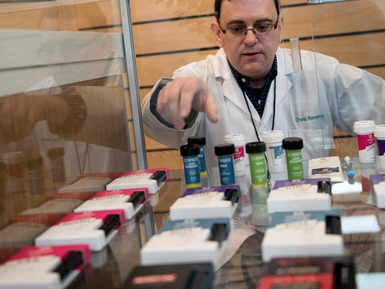 Eric Hauser, president and CEO, looks over a showcase of empty sample boxes, at the new medical marijuana dispensary, Organic Remedies at 900 Wayne Avenue, Chambersburg. The case that will contain cannabis products when the store opens later this month.