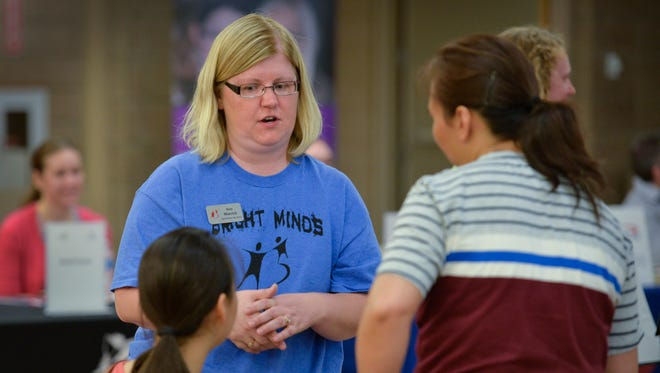Ann Matvick, program director with Big Brothers Big Sisters of Central Minnesota, talks with participants in a career exploration night Tuesday, June 21, at St. Cloud Technical & Community College.