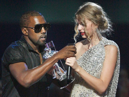 Kanye West takes the microphone from Taylor Swift as