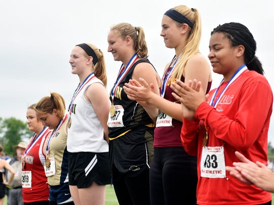 Red Lion's Madisen Kling, center, stands at the top of the podium after winning gold in the Class 3A discus throw in the PIAA track and field meet Saturday, May 27, 2017, at Shippensburg University.