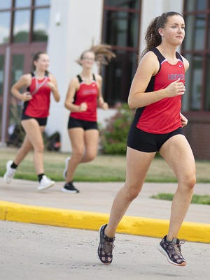 United High School senior Bridget Brokaw joins her teammates in a run during cross country practice Monday afternoon.