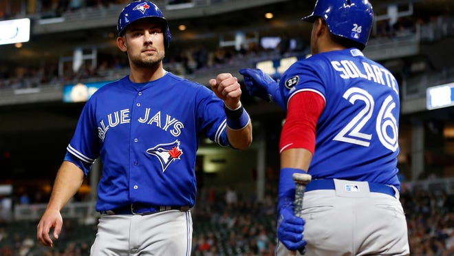 Toronto Blue Jays' Luke Maile, left, is congratulated by Yangervis Solarte after Maile scored on a single by Justin Smoak during the fifth inning of a baseball game Tuesday, May 1, 2018, in Minneapolis. (AP Photo/Jim Mone)