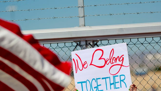 A protester holds a sign outside a closed gate at the Port of Entry facility, Thursday, June 21, 2018, in Fabens, TX., where tent shelters are being used to house separated family members. (AP Photo/Matt York)