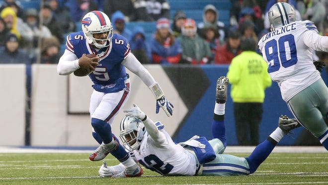 Bills quarterback Tyrod Taylor slips away from pressure by Dallas safety Barry Church (42) in a 16-6 Buffalo win.