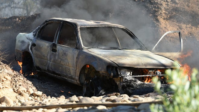 Flames burn a car then spread to vegetation Saturday evening off Canyon Road.