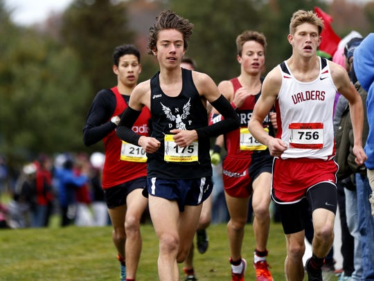 Miguel Mathias, left, battles Valders' Cody Meyer lead race near the one-mile mark in the Division 2 boys race during the WIAA state cross country meet Saturday.