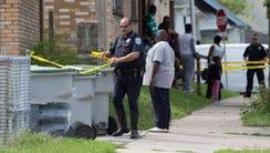 A police officer strings crime scene tape near the