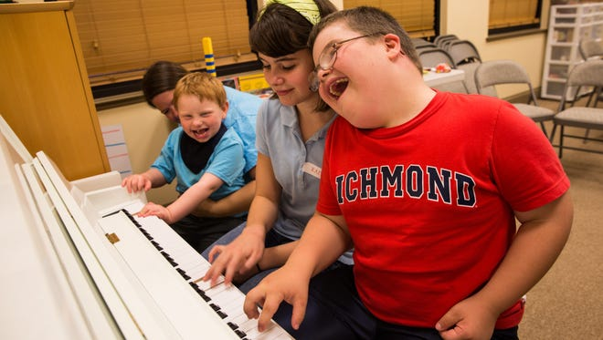 Ian Angiuoli, 10, from right, laughs with his sister Kaitlyn Angiuoli, 13, and Garrison Betz while playing the piano during Buddy Break at Naples Seventh-day Adventist Church on August 19, 2016. Nathaniel Hope's Buddy Break is a free respite program that provides a break for parents and caregivers of special needs children and their siblings. In celebration of the Olympics, they hosted an Olympics theme this time with crafts, games, prizes, a balloon arch and balloon animals.
