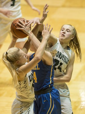 Zionsville High School junior Sarah Howell (10), left, and junior Maddie Nolan (24) pressure Carmel High School junior Macy Berglund (44) during the second half of the championship game of the Girls' Hall of Fame Classic tournament, Friday, December 29, 2017, at New Castle High School. Carmel won 75-51.