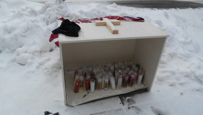 A shrine with candles is set up at the Town & Country Apartments complex in Binghamton, where Santos Echevarria was fatally stabbed.