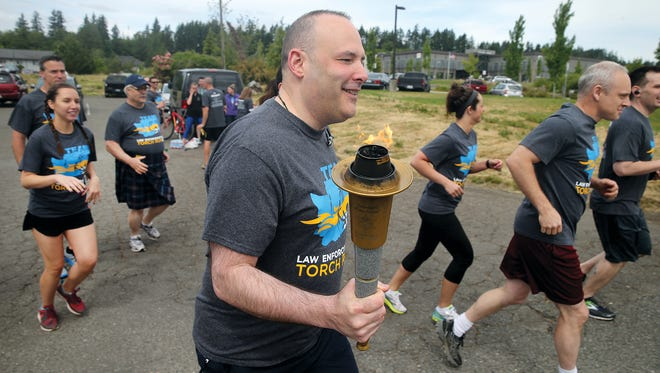 The Kitsap County Sheriffs Office Special Olympics torch running team member officer John Sackman and the team head off on their running leg on Thursday. The KCSO took the torch from NCIS at Silverdale Way near the Haselwood YMCA.