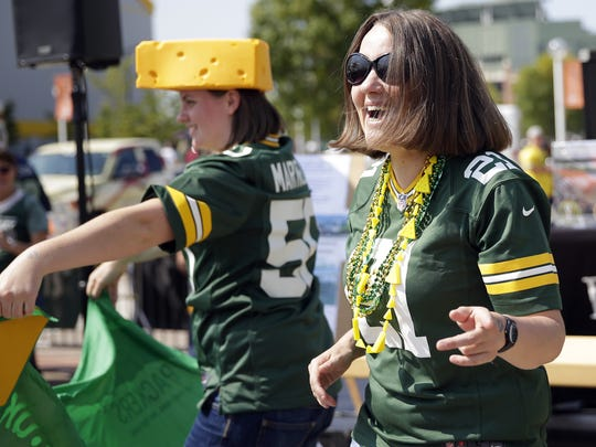 Gillian Briggs (right) and Charlotte Midgley, both of Leeds, England, dance during a tailgating party outside the Resch Center in Ashwaubenon, Wis. before the Packers vs. Seattle Seahawks game on Sept. 10, 2017 at Lambeau Field. The women are members of the UK and Irish Packers fan group.