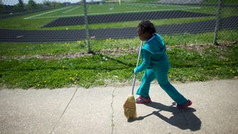 Kailah Johnson, 5, a pre-k student home from school with citywide closure, joined in a neighborhood cleanup.