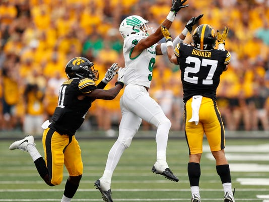 Iowa defensive back Amani Hooker (27) and defensive back Michael Ojemudia, left, break up pass intended for North Texas wide receiver Jalen Guyton, center, during the first half of an NCAA college football game, Saturday, Sept. 16, 2017, in Iowa City, Iowa. (AP Photo/Charlie Neibergall)