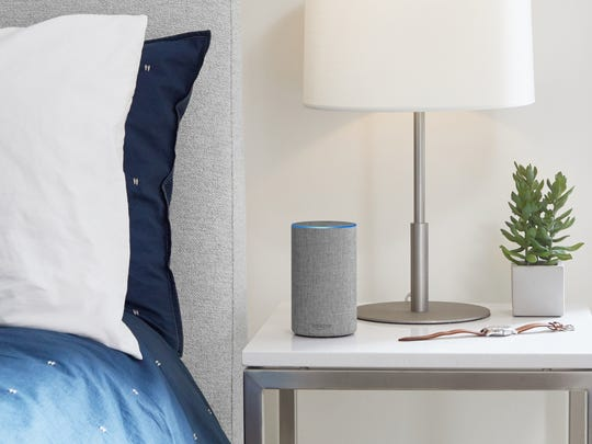 A gray Amazon Echo on a bedside table.