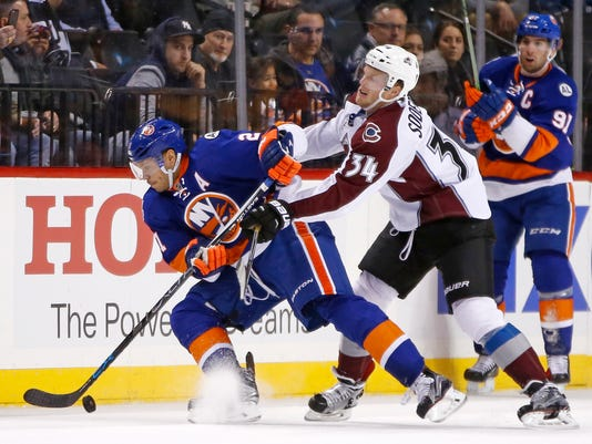 Colorado Avalanche center Carl Soderberg (34) checks New York Islanders right wing Kyle Okposo (21) in the first period of an NHL hockey game in New York, Monday, Nov. 30, 2015. (AP Photo/Kathy Willens)
