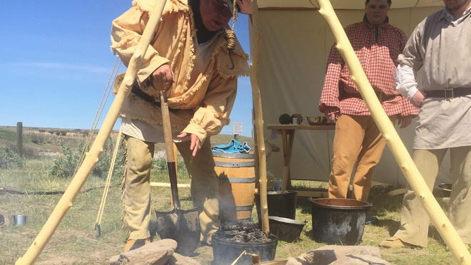 John Toenyes stirs embers at a cooking demonstration at the Lewis & Clark Interpretive Center on Sunday afternoon.