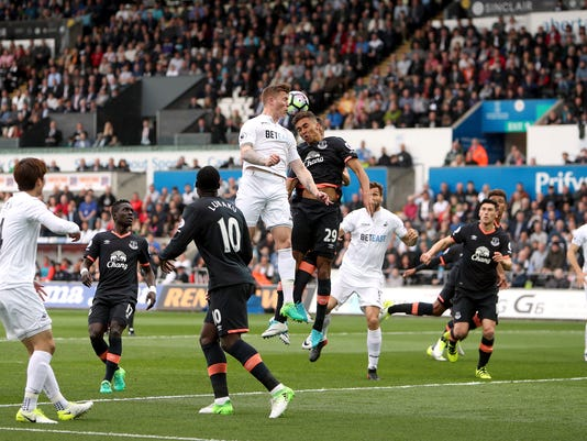 Swansea City's Alfie Mawson, centre left, and Everton's Dominic Calvert-Lewin, centre right, challenge for the ball during the English Premier League soccer match, Swansea City against Everton at the Liberty Stadium, Swansea, Wales,  Saturday May 6, 2017. (David Davies/PA via AP)
