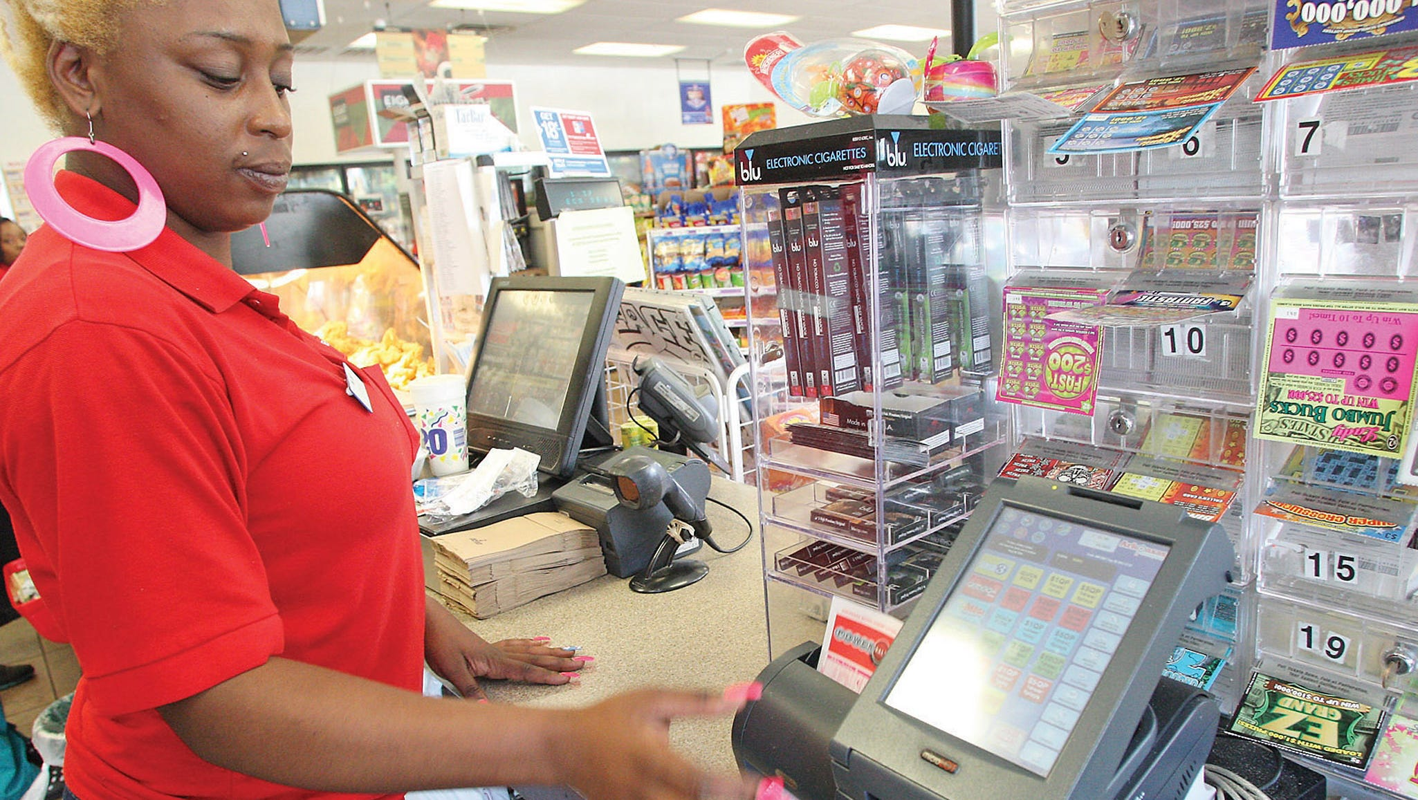 Meykai Howell runs a Powerball ticket through a machine at the Expressway #672 on East Main Street on Aug. 6 in El Dorado, Ark.