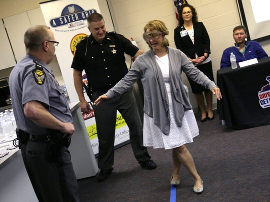 Tracy Anderson attempts to walk a line while wearing fatal vision goggles in front of Highway Patrol Lt. Mike Vinson.  The event was to help raise awareness of increased patrols of impaired driving.
