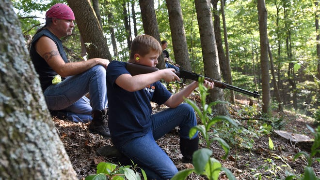 Dana Lake, left, watches over his children Ross Lake, 11, and Alivia Lake, 12, as they shoot at targets to practice for squirrel hunting season near their Chandlersville home. Squirrel hunting season began Sept. 1 and runs through Jan. 31. The siblings have already bagged one squirrel each.