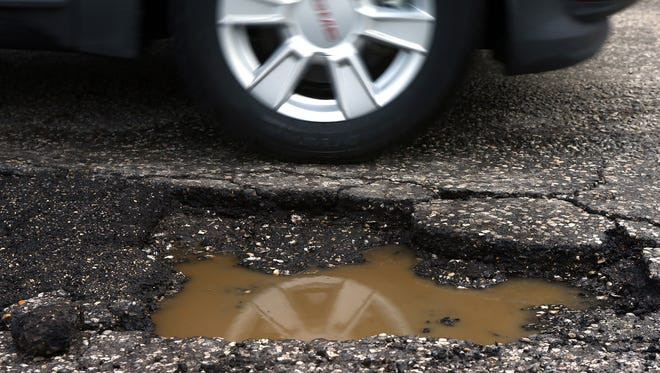 A vehicle drives past a pothole located near a bus stop on Morgan street Thursday Feb. 5, 2015 in Corpus Christi.