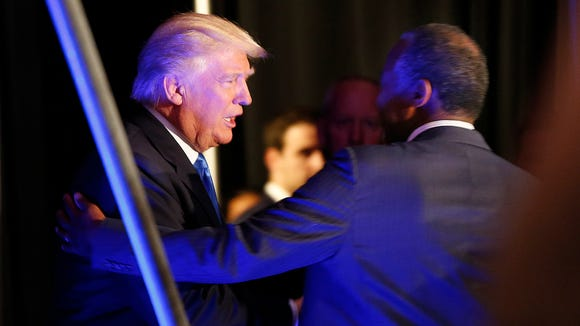 Donald Trump greets Ben Carson as he arrives to speak
