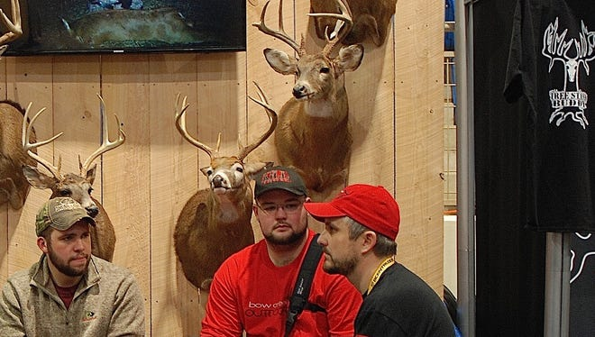 Pro staff members of Palmyra's Bow Creek Outdoors prepare for another busy day in the archery hall at the NRA Great American Outdoor Show in Harrisburg.