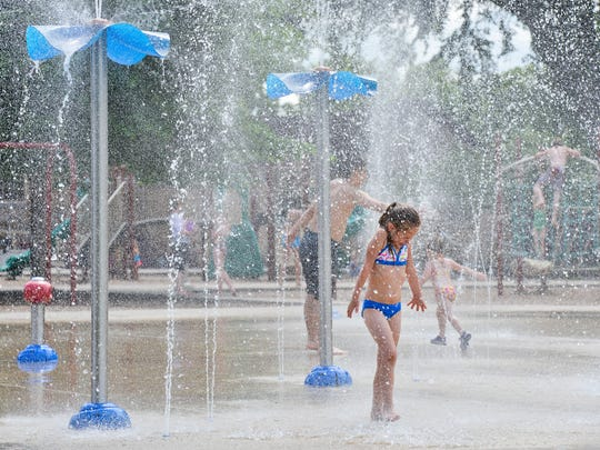 Daisie Jean Strassburg, 6, reacts to a heavy spray of water from the plethora of water jets Thursday, June 9, 2016, at the Lake George splash pad. Strassburg is from Bertram and it was her first time to experience a splash pad since her hometown doesn't have one.