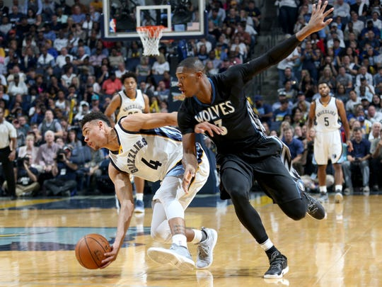 Memphis Grizzlies Wade Baldwin IV scoops up a loose ball defended by Minnesota Timberwolves Kris Dunn.