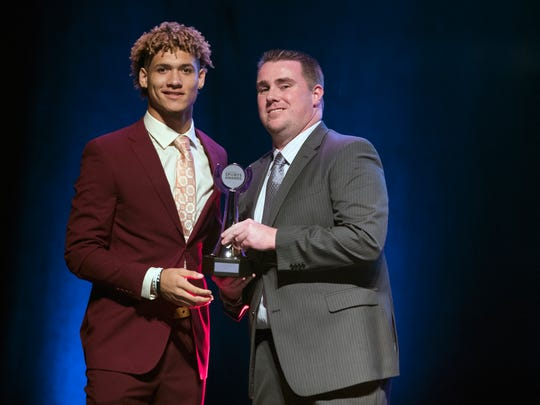 South Fort Myers High School's Jeshaun Jones accepts The News-Press Football Offensive Player of the Year award from sports writer Adam Regan recently at the Southwest Florida Sports Awards in Fort Myers.
