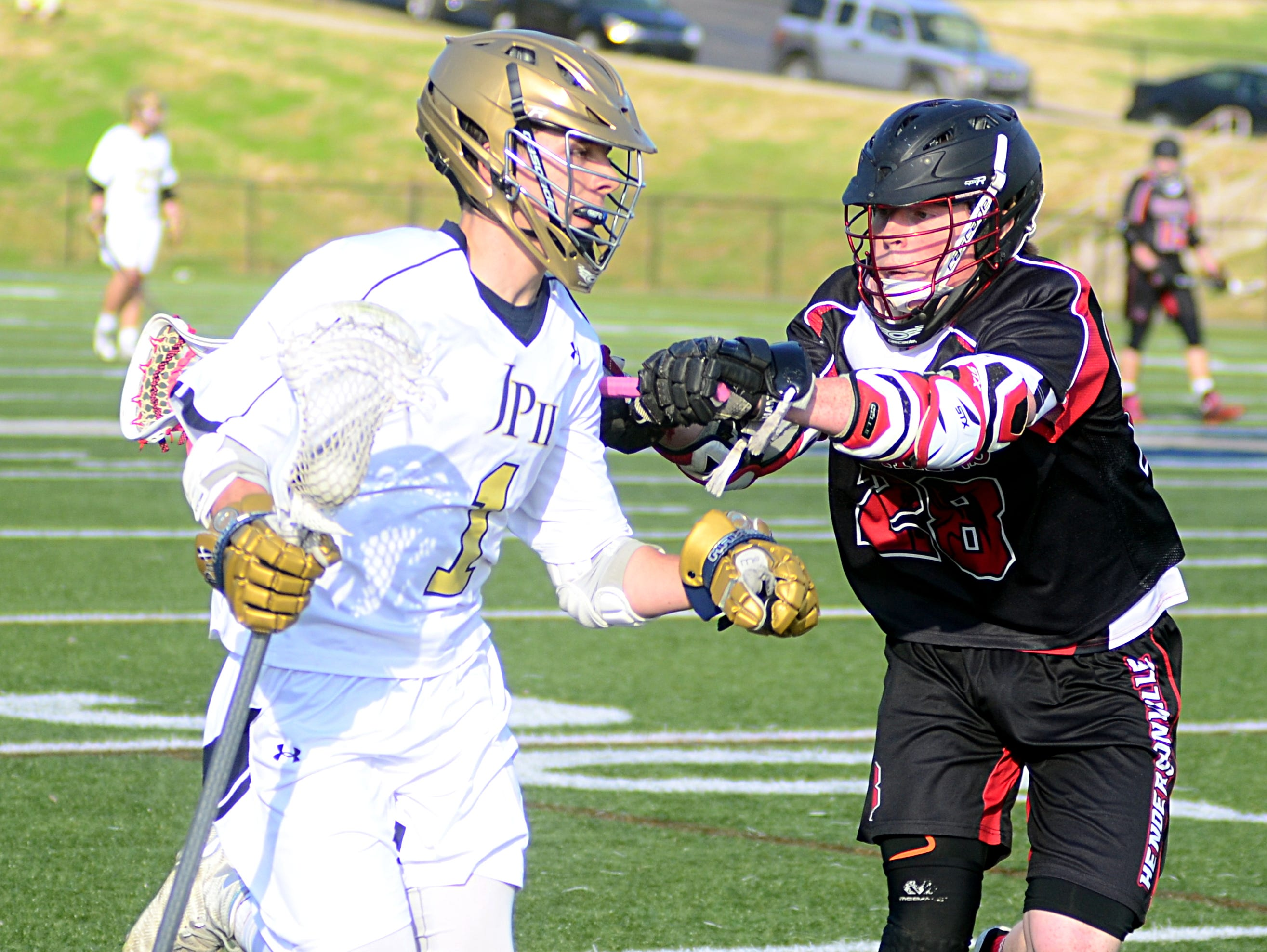 Pope John Paul II High sophomore midfielder Nolan Underhill absorbs a stick check from Hendersonville Spartans senior Fredrick Thacker during first-quarter action. Underhill scored twice in the Knights' 17-4 victory.