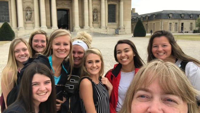 A group of students and parents pose while they take in the sights around Europe. They visited famous places like the Louvre, Palace of Versailles and the Swiss Alps.