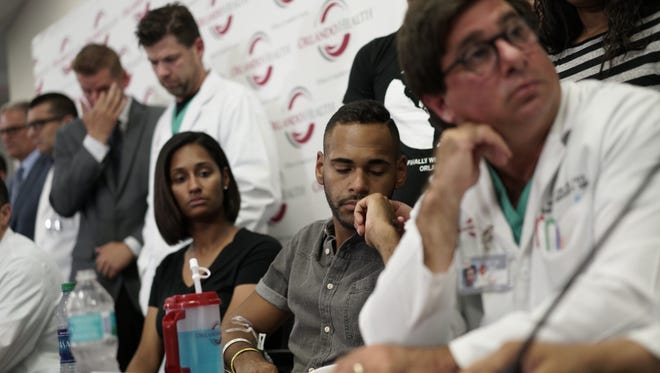 Angel Colon, center,  a survivor of the Orlando nightclub shooting, attends a press conference at Orlando Regional Medical Center on June 14, 2014l