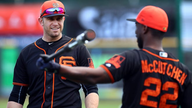 San Francisco Giants' Evan Longoria, left, speaks with Andrew McCutchen (22) during a spring training baseball practice on Monday, Feb. 19, 2018 in Scottsdale, Ariz.