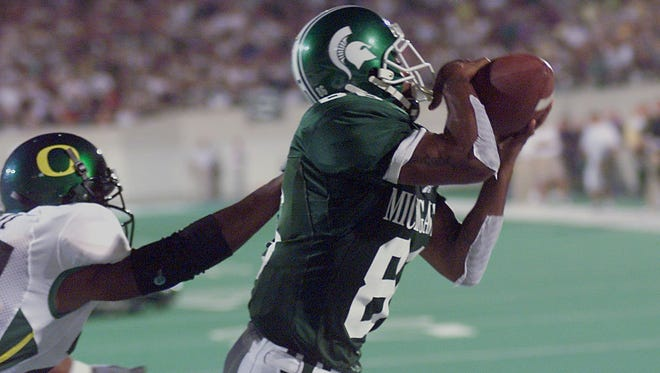 Spartan wide receiver Gari Scott, right, hauls in the game-tying touchdown pass late in the third quarter against Oregon in 1999.  (LSJ file)