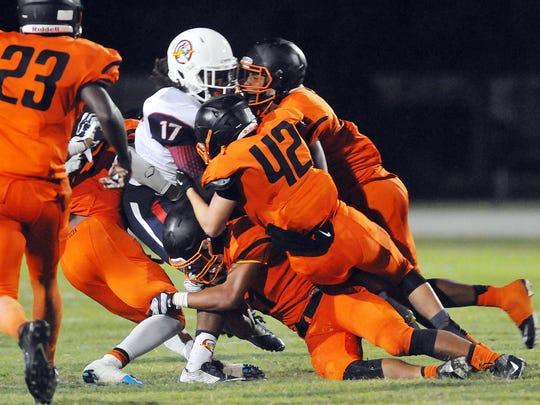 Oxbridge Academy's Cajuan Smith is hammered in the backfield by a host of Cocoa High defenders during Thursday nights spring football game held at Cocoa Stadium.