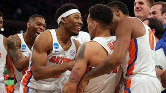 The Florida Gators celebrate with guard Chris Chiozza (11) after he hit the game winning the shot to beat the Wisconsin Badgers during overtime in the semifinals of the East Regional of the 2017 NCAA tournament at Madison Square Garden.