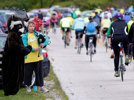 Eco, the raccoon, left, and Mary Lynne Donahue (playing bagpipes) wave off bicyclists on the 16th annual Earth Ride at Ellwood H. May Environmental Park Saturday September 19, 2015 in Sheboygan.